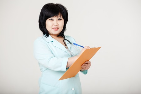 patient data: Asian brunette nurse with stethoscope around neck and folder in her hands ready to record patient information, provides a diagnosis. Registry, medical data entry, record. On reception at doctor.