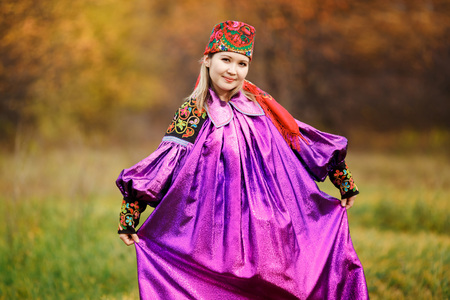 smartly: Beautiful girl in national dress smartly in blue with ornaments and embroidery, posing on a background of yellow leaves. Colorful bokeh in the autumn nature. Design with copy space for your text.