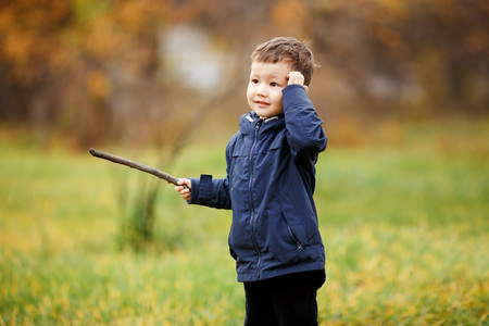 wooden stick: Cute boy with wooden stick in his hand playing in autumn park outdoors. He stopped to think what to do, looking to the side. Fall, yellow leaves in bokeh. Kid wearing blue jacket. Carefree childhood.