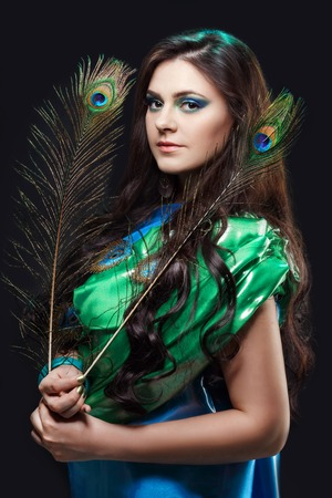 harmonious: Beauty portrait of beautiful girl covering the eyes of a peacock feather. Creative makeup peacock feathers. Attractive mysterious interesting lady. Perfect holiday expressive artistic makeup peacock feathers. Bright colors, harmonious green black yellow b