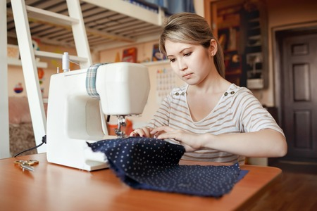 machine tool: Young woman sewing with sewing machine at home while sitting at her working place. Fashion designer carefully creating new fashionable styles. Dressmaker makes clothes via additional part-time job. Stock Photo