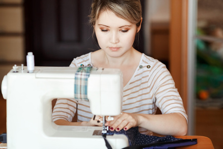 modiste: Young woman sewing with sewing machine at home while sitting at her working place. Fashion designer carefully creating new fashionable styles. Dressmaker makes clothes via additional part-time job. Stock Photo