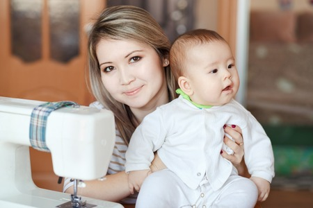 looking directly at camera: Baby with his mother at home, natural light, curiously looking directly into the camera. Near the sewing machine. Child care and work at home.