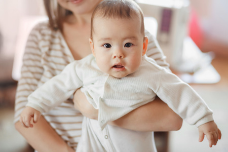 beautiful boy: The cute little baby boy in the arms of mom on the air. Mother and infant, infant care, children and kids growing. Interestedly looks directly into the camera. Stock Photo