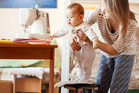 work from home: Mother and infant at home, the first baby steps, natural light. Child care and work at home.