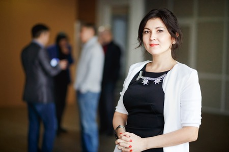 is real: Successful attractive boss brunette with kind eyes stands inside office building and welcoming smile. Strict black dress jewelry. Cute young business chief woman posing. In the background man discussing. Stock Photo