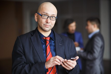 straight man: Portrait of a man with glasses businessman with phone in hand, dressed in a striped suit and red tie, stands inside office building. He looks straight into camera. In the background man discussing. Stock Photo