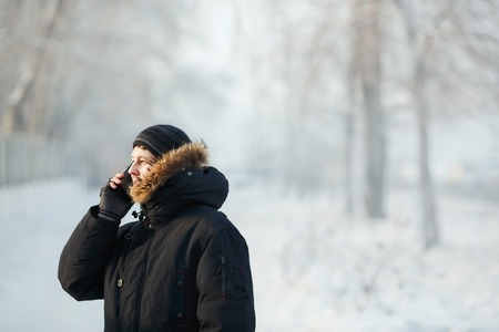 fur hood: Young Siberian man talking on the phone outdoors in the cold by day in a warm winter down jacket with fur hood. Snow frost, communication in any weather. Place for your text.