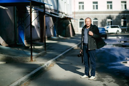photo story: Full height portrait of brutal photographer in street with camera in hand, in yard apartment buildings, photo backpack, wearing  jacket, sunny spring weather. In search of plot, story for photography.