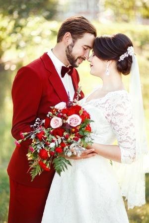 Marsala bruidspaar, bruid en bruidegom omarmen, donkerrode kleur style design. Pak met kastanjebruin vlinderdas, witte jurk, bruidsboeket. Professionele make-up. Eeuwige liefde, tederheid, schoonheid concept. Stockfoto