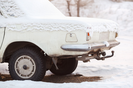metal processing: The rear of the car trunk covered with snow in winter, old broken white color at sunset. Recycling, metal processing, write-off of cars.