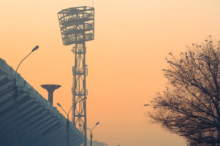 turned: City background silhouette stadium spotlights, bowl for the olympic torch and tree covered with snow at sunset. Stadium lights turned off at twilight time. Winter season, cold weather. Editorial