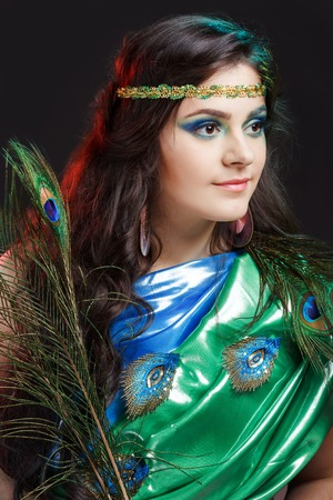 sexy young woman: Beauty portrait of beautiful girl covering the eyes of a peacock feather. Creative makeup peacock feathers. Attractive mysterious interesting lady. Perfect holiday expressive artistic makeup peacock feathers. Bright colors, harmonious green black yellow b