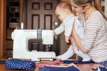 learns: A small child learns new knowledge, they, along with her mother inspecting the sewing machine. Work at home, parenting, parents and children, child care, babysitter. Stock Photo
