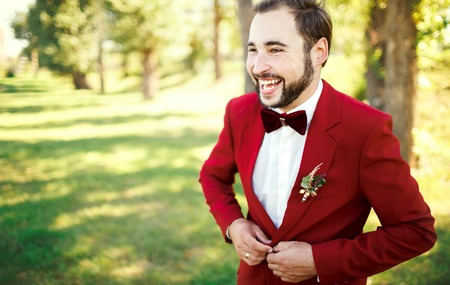 man in tuxedo: Stylish groom portrait in tuxedo suit marsala red, burgundy bow tie, a professional hairstyle, beard, mustache. Wedding preparations, groom getting ready. Copy space for text. Celebration.