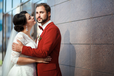 romantic man: Bride and groom, romantic wedding couple in a passionate outburst, near the walls of the building.  Red suit with a buttonhole, man with a stylish beard, mustache and bow tie. Medium shot, copy space.