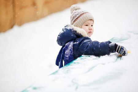 fraternidad: El ni�o peque�o que juega solamente en la nieve, de cerca. Fuera de. mitones de desgaste, sombrero y chaqueta abajo. La soledad, la amistad y la hermandad.