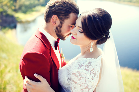 photo shoot: Bride and groom, lovely couple, cuddling on the waterfront, a photo shoot after the wedding ceremony. Stylish man with mustache, beard and bow tie, in purple red suit. Wedding Color Marsala. Toned. Stock Photo