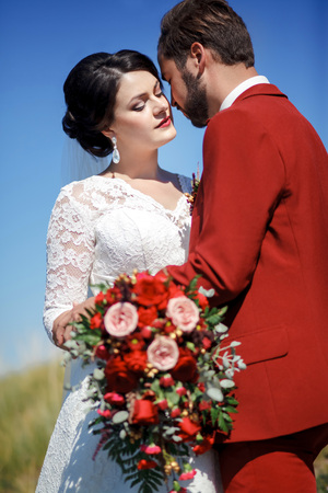 great suit: Bride and groom, lovely couple outdoor, great chic wedding bridal bouquet with red flowers. Blue sky and green grass.  Vertical beauty portrait of a couple. Stylish man with beard and mustache in red suit. Wedding Color Marsala.