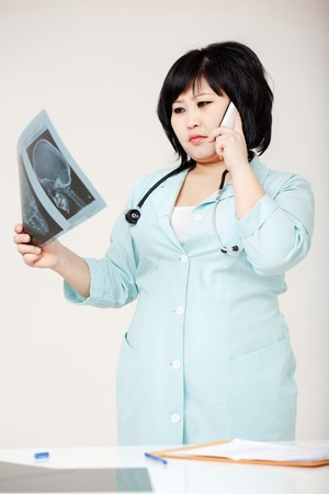 x ray equipment: Asian woman doctor in a robe discussing diagnosis talking on the phone, considering the X-ray picture. Medical mistake, the medical commission. Stethoscope around her neck.