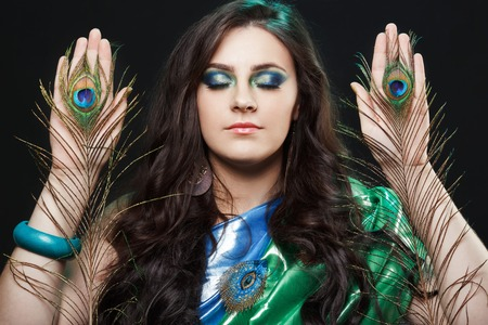 psychics: Psychic abilities psychics communicate with spirits. Beauty portrait of girl with peacock feathers, bright clothes, creative makeup. Bright colors, harmonious green black yellow blue. Dress in the style of sarees, shiny satin silk fabric.