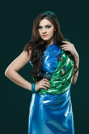 sexy young woman: Woman in a brilliant blue-green dress with peacock feathers in the design. Creative fantasy makeup, long dark hair. Stock Photo