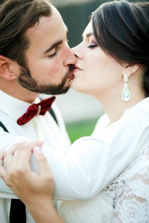 hombres jovenes: La novia y el novio besando. Pares de la boda, la novia y el novio. Retrato cercano. El hombre de la pajarita y tirantes.