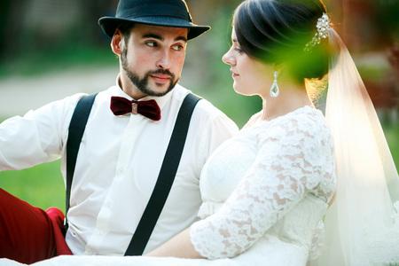 uomini belli: sposa e lo sposo alla moda si siede sull'erba in raggi del sole. Uomo in cappello con cravatta e bretelle arco, pantaloni rossi guarda languidamente una donna con styling dei capelli professionale. Un paio di sposi.