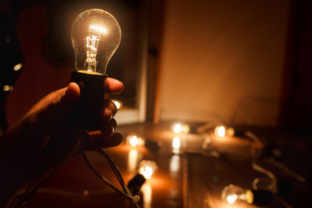 Incandescent light bulb, a warm light turned on in the dark, in the hands of a person. Garland of tungsten lamps. The light in the darkness, copy space. Stock Photo
