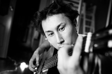unrestrained: Crazy passionate guitarist playing guitar, black and white close-up portrait. Stock Photo