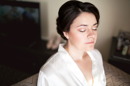 nude girl young: Bride with closed eyes showing bridal makeup in the morning in a white silk robe. Wedding preparation. Stock Photo