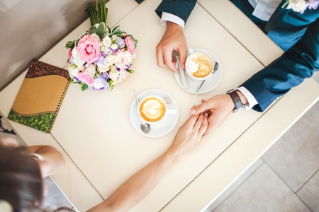 romantic date: Wedding couple at the cafe, top view. Man holds womans hand and drinks espresso. Bride and groom coffee break dating gift, bouquet on the table. Stock Photo