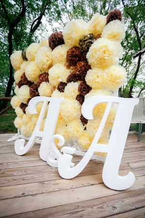 pompon: Flower pompon backdrop wall, wedding decoration zone with double letters a. Yellow white and brown color. Vertical. Stock Photo