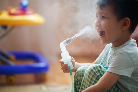 bebe enfermo: El niño pequeño hace la inhalación en casa, tomar la medicación a los tubos bronquiales. Exhala vapor a través del tubo.
