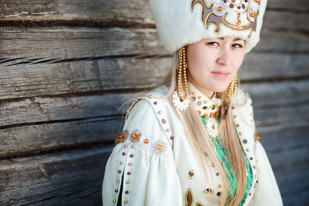 boyar: Portrait of a young woman in traditional dress of the peoples of South Siberia, against the wall of timber.