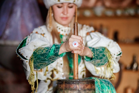 producing: Young woman in traditional siberian dress producing butter from milk at home, inside the yurt.