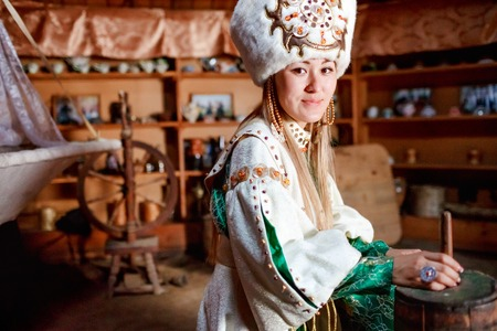 kyrgyz republic: Portrait of a cute young woman in traditional yurt dwelling of Siberian peoples dressed in ethnic attire. Stock Photo