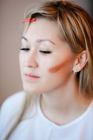 cheekbones: Model while applying makeup, contouring cheekbones. Preparation of the bride in the morning. Stock Photo