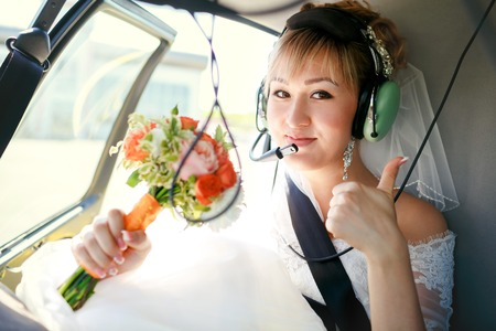 Bride inside a helicopter preparing to fly in the headset and with a wedding bouquet showing thumbs up.