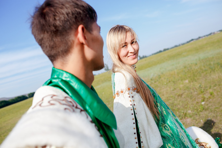 stage costume: Loving couple in traditional attire walking in a field on a sunny summer day, stage costume.