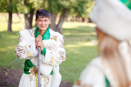 leaned: A man in a traditional festive dress of steppe nomads, leaned on his cane, looking at his wife.