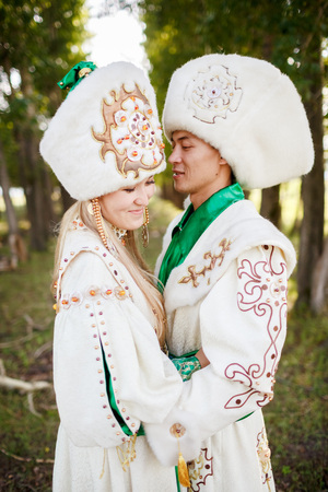 wedding parade: Couple in ethnic clothes outdoors, holding hands.