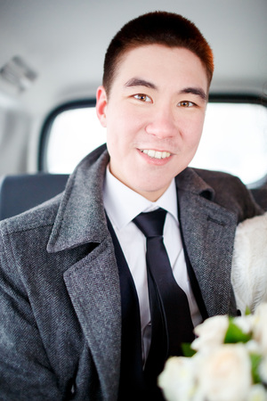 tailor seat: The groom in a winter coat sitting in the car with wedding bouquet in hands. Positive portrait, looking into the camera. Stock Photo