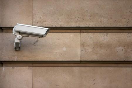 CCTV camera on stone-clad wall Stock Photo