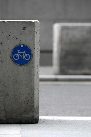 Blu pista ciclabile segno su blocco di cemento Archivio Fotografico