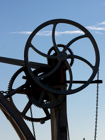 Silhouette of cogs, wheels and chains against a blue sky Stock Photo