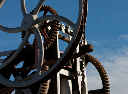 Cogs, wheels and chains against a blue sky Stock Photo