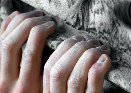 Chalked fingers hang off an artifical climbing hold. Shallow depth of field