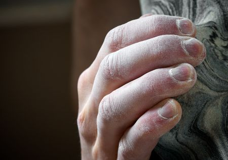 Chalked hand grips tightly to hang off an artifical climbing hold. Shallow depth of field