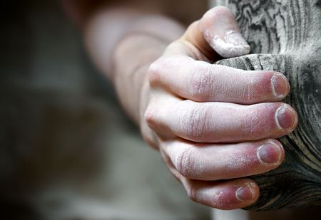 Chalked hand grips tightly to hang off an artifical climbing hold. Shallow depth of field photo